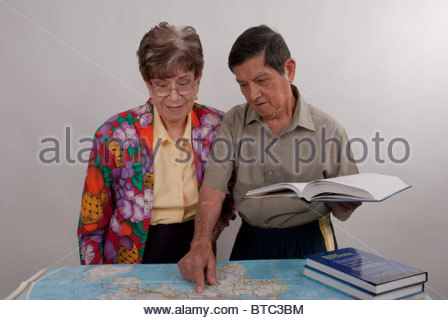 Elderly couple studying geography at the world map. - Stock Image