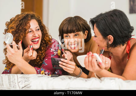 Three cheerful young women at home getting ready with red lipstick make up lay down on the bed in friendship and laughing a lot - people have fun - fr - Stock Image