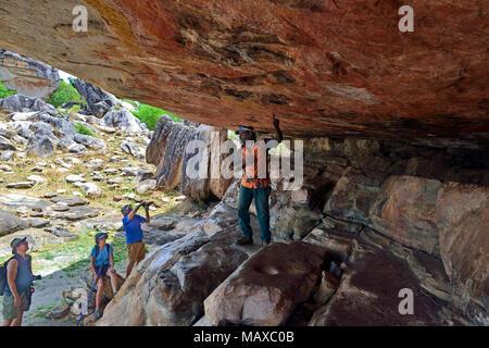 Aboriginal tour guide points out rock art to tourists on Anjalak Hill, near Gunbalanya, Arnhem Land, Northern Territory, Australia - Stock Image