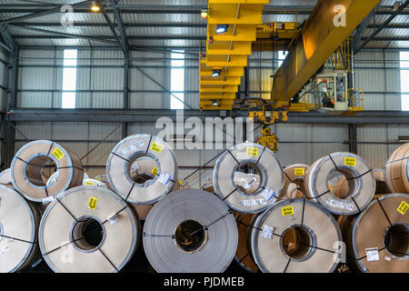 Crane over rows of sheet steel in storage at port - Stock Image