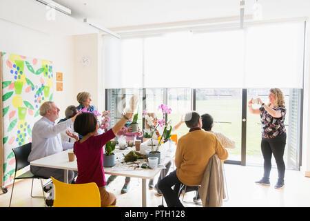 Instructor photographing active seniors enjoying flower arranging class - Stock Image
