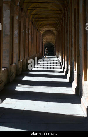 A woman wearing sunglasses walking down the Portico di San Luca in Bologna, Italy. Reputedly the longest portico - Stock Image
