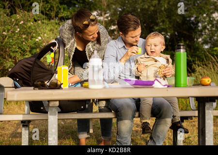 Family by picnic table - Stock Image