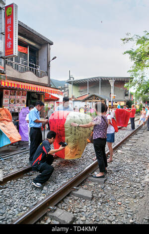 SHIFEN, TAIWAN -JUL 15, 2013: Visitors wrote their wishes on sky lanterns and prepared for launch on the railway tracks of Shifen Old Street in Taiwan - Stock Image
