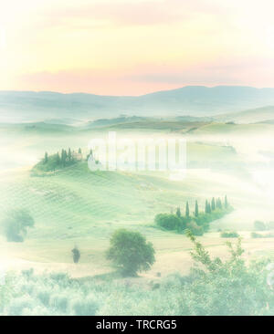 Dawn in a misty valley with view on Bevedere villa in the hills near Pienza - Stock Image