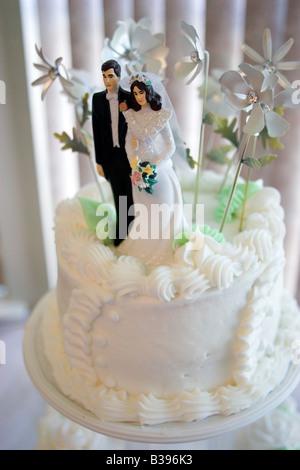 A bride and groom figurine tops a wedding cake. - Stock Image
