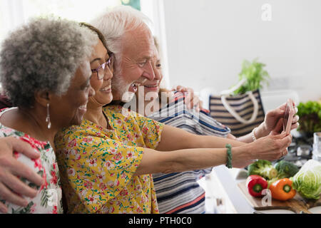 Happy senior friends taking selfie with camera phone - Stock Image
