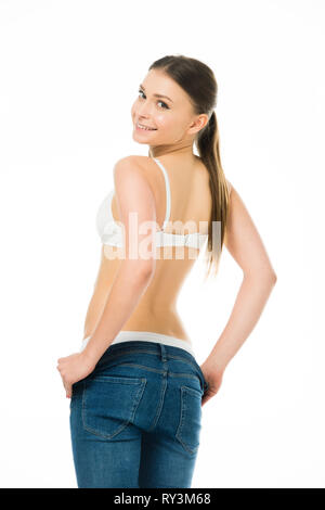smiling slim woman taking off blue jeans isolated on white - Stock Image