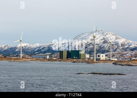Wind turbines driving electric powered generators at a small industrial site in the Norwegian fjords. - Stock Image