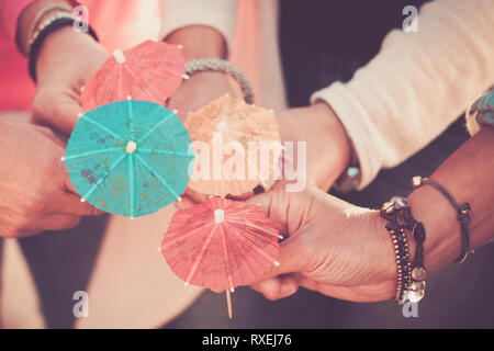 Close up women's hands together with umbrella cocktail for summer style concept and vacation in friendship  colours and happiness with group of people - Stock Image