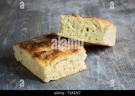 Italian bread of Focaccia Genovese type on a rustic wooden table, sliced in two squared pieces. The focaccia is a traditional oven baked flat bread, t - Stock Image
