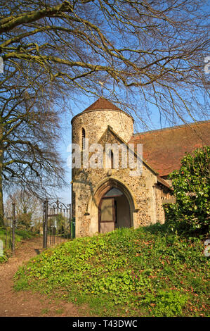 A view of the round tower and south porch of the parish Church of All Saints at Freethorpe, Norfolk, England, United Kingdom, Europe. - Stock Image