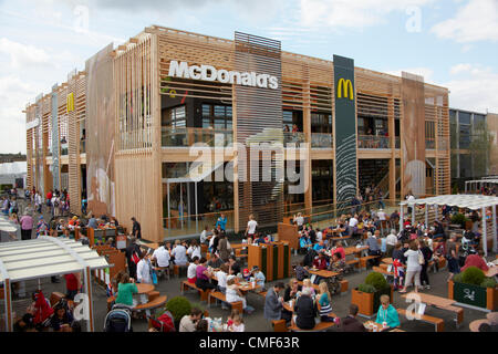 People eating outside in sunshine at a MacDonalds Restaurant at Olympic Park, London 2012 Olympic Games site, Stratford - Stock Image