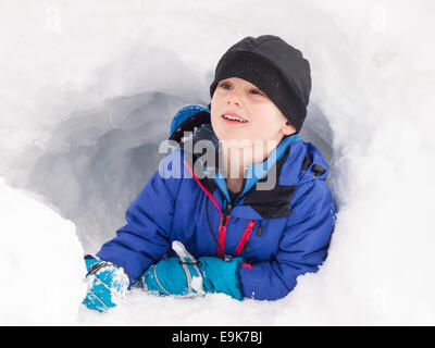 small smiling boy in winter clothes playing in a snow hole - Stock Image