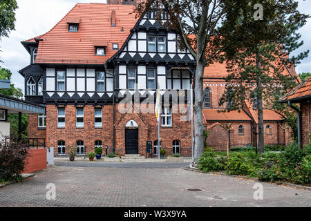 Holy Family Church, Berlin-Lichterfelde, Red Brick Gothic revival-style building with tudor-style detail designed by Architect Christoph Hehl and buil - Stock Image