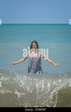 a girl standing in a lake in the waves - Stock Image