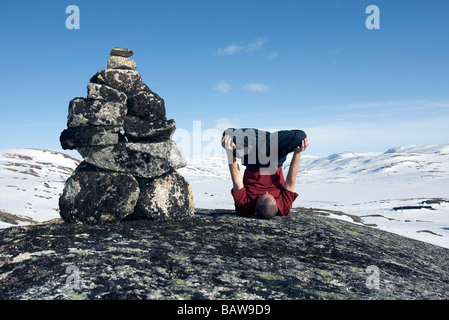 Doug Blane performing an Urdhva Padmasana besides a cairn in Finse Norway in winter - Stock Image