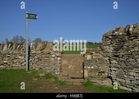 Stone stile and footpath sign in the Cotswold village of Swinbrook near Burford, Oxfordshire - Stock Image