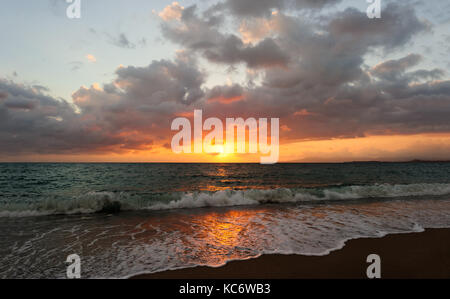 Ocean sunset is an ocean sunset wave rolling to shore as the sun sets on the ocean horizon. - Stock Image