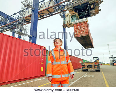 train dock worders talking while cargo is loaded to lorry waiting by port crane - Stock Image