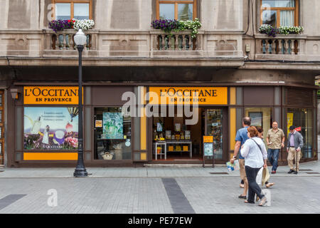 Gijon, Spain - 6th July 2018: people walking past L'Occitane en Provence shop. The company is an international retailer of body and face, fragrances - Stock Image