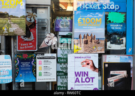 Lottery ticket and mibile phone top up adverts posted pasted on the window of a newsagent shop in London England UK  KATHY DEWITT - Stock Image