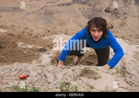 Young teenage boy fully clothes running up a sandbank, Marengo beach, Vic, Aus. - Stock Image