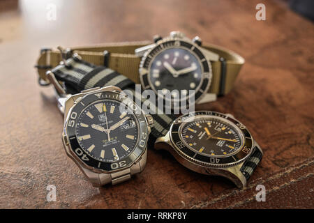 Group of men's luxury diver style wristwatches or timepieces on a dark wood background. - Stock Image