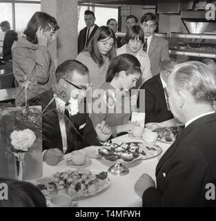 1967, historical, promotional, Miss United Kingdom 1967 signing authographs for the staff in a company canteen whilst having tea and cakes with the directors of the Energen Company, England, UK. - Stock Image