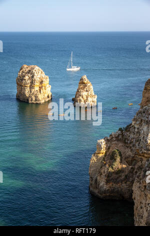 Algarve, sea stacks, kayak and boat. Portugal - Stock Image
