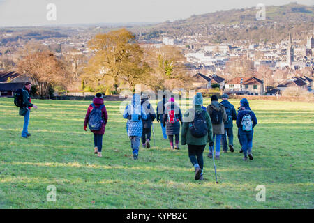 A group of walkers on a bright winter day walking across National Trust park towards the historic city of Bath with - Stock Image