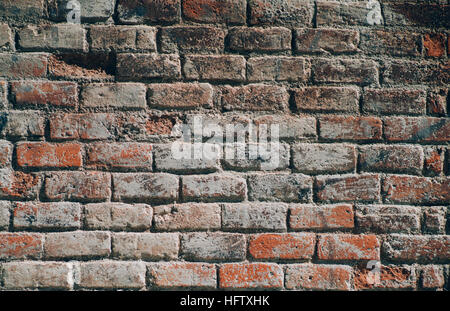 Red dirty brick wall architectural background texture with burned black areas on sunny summer day, Barcelona, Spain - Stock Image