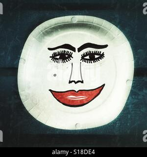 Face drawn on a paper plate. - Stock Image