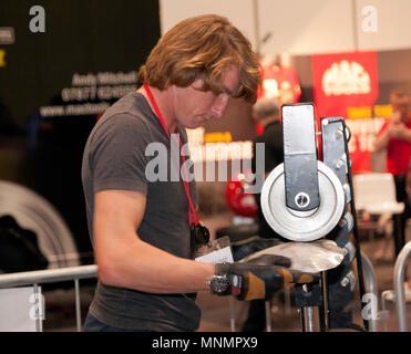 Racing driver Freddie Hunt learning how to using a wheel to shape a metal panel, at the Car S.O.S. area, during the  London Motor Show 2018. - Stock Image