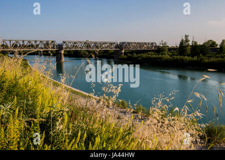 A large river with a bridge with railway tracks landscape - Stock Image