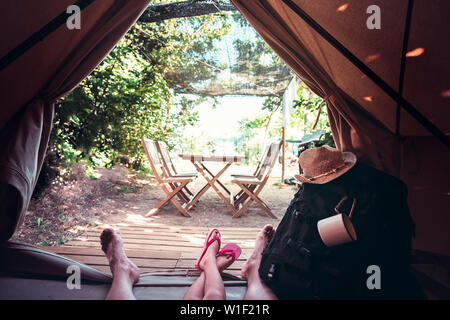 view of the legs of a hiker man with a kid resting barefoot in a camping tent, travel discovery concept, point of view shot - Stock Image