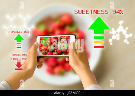 Woman holding a smart device uses reality augmentation to examine the ripeness of a bowl of strawberries - Stock Image