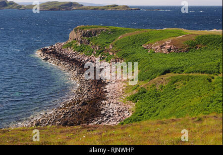 A view out to sea and the Summer Isles from near Dornie, Polbain, Scotland on a warm sunny summer's day with blue sea and a headland in the foreground - Stock Image