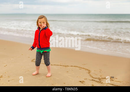 Colour portrait of young girl at the beach joyfully showing sand on finger to camera after doodling in sand. Poole, Dorset, England. - Stock Image
