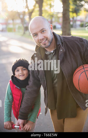 Portrait father and son with basketball in autumn park - Stock Image