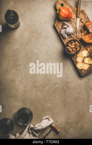 Wine and snack set. Flat-lay of wine bottle, two glasses of red wine, vintage corkscrews, cheese and appetizers on wooden board over dusty concrete ba - Stock Image