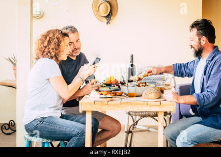 Three adults middle age friends have lunch together at the restaurant in rural place - wood table and concept of friendship - home leisure activity wi - Stock Image
