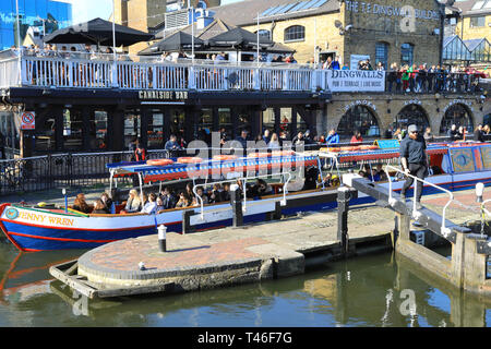 Barge with tourists passing through Camden Lock on the Regents Canal, in spring sunshine, in north London, UK - Stock Image