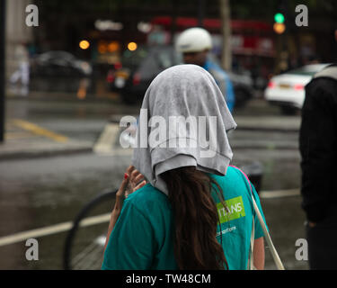London, UK. 18th June 2019.  Rain in London: if you don't have an umbrella or a raincoat you just use a shirt to protect your hair in the rain. Tourists and Londoners protecting themselves against the continuous rain in central London today. Credit: JoeKuis / Alamy - Stock Image
