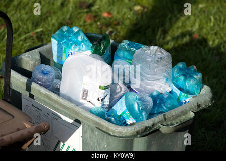 A local authority waste recycle outside a house for collection and recycling. It's full of assorted packaging plastics - Stock Image
