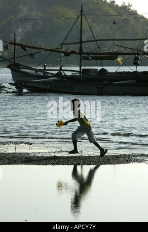 A child plays on the beach in the early morning in Mansalay, Oriental Mindoro, Philippines. - Stock Image