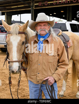 Portrait of cowboy with his horse in traditional western wear including a cowboy hat in Montgomery Alabama, USA. - Stock Image