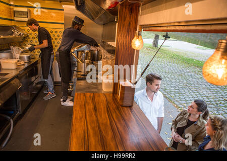 Customers waiting in front of counter of food truck - Stock Image
