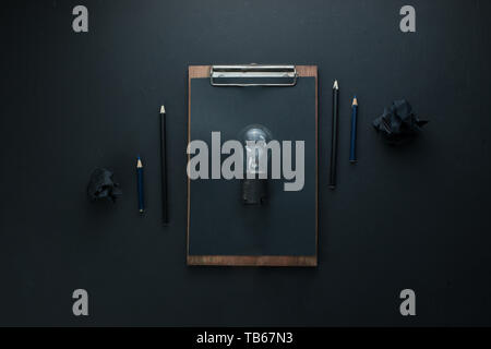 Building and construction concept, the light bulb of an idea on a dark background with crumpled paper balls and pencils. - Stock Image
