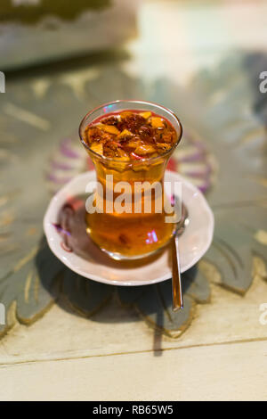 A clear glass cup of traditional Turkish apple tea with bits of apple floating in the drink on a white saucer with teaspoon, Istanbul, Turkey - Stock Image